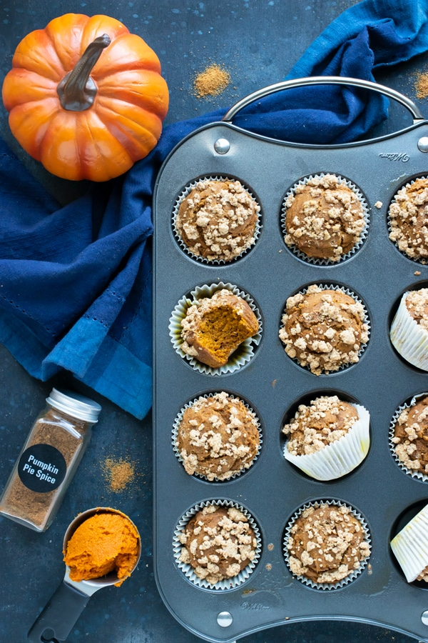 A tray full of an easy pumpkin muffin recipe next to a bottle of pumpkin pie spice and pumpkin puree.