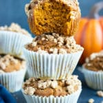 Three gluten-free pumpkin muffins stacked on top of each other surround by other healthy, vegan, and easy pumpkin muffins.
