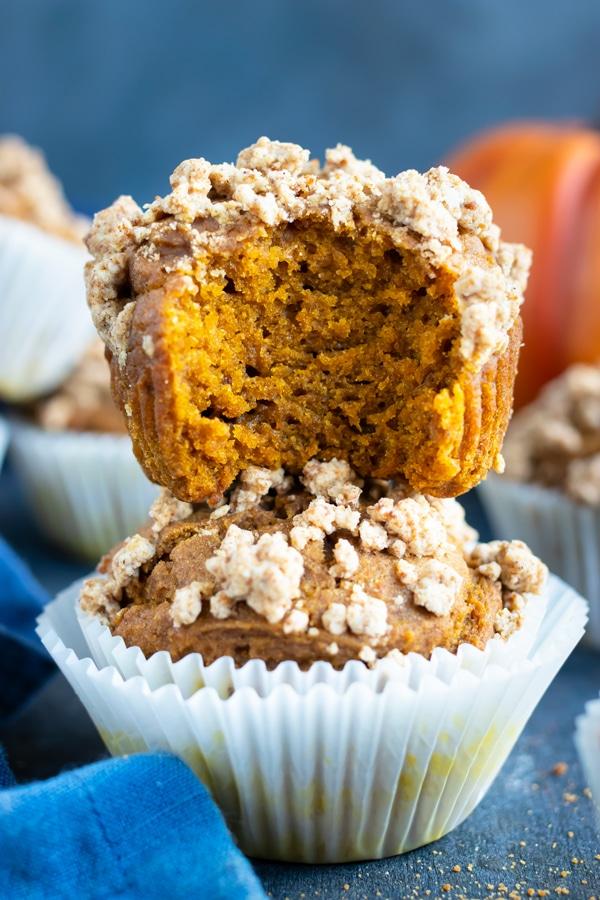 A big bite that has been taken out of a gluten-free pumpkin streusel muffin.