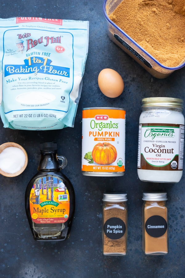 Gluten-free pumpkin muffin recipe ingredients laid out on a black background.