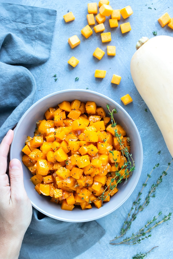 A serving bowl full of butternut squash that has been baked in the oven for a healthy Thanksgiving side dish recipe.