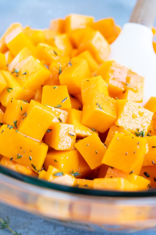 Cubed butternut squash being tossed in a maple garlic and herb sauce.