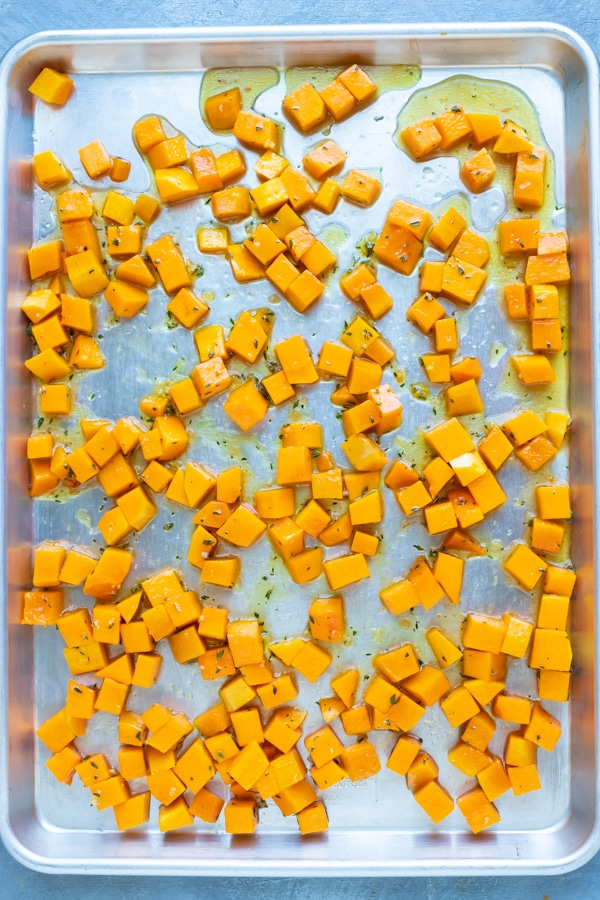 Cubed butternut squash on a baking sheet in a single layer to be roasted in the oven.