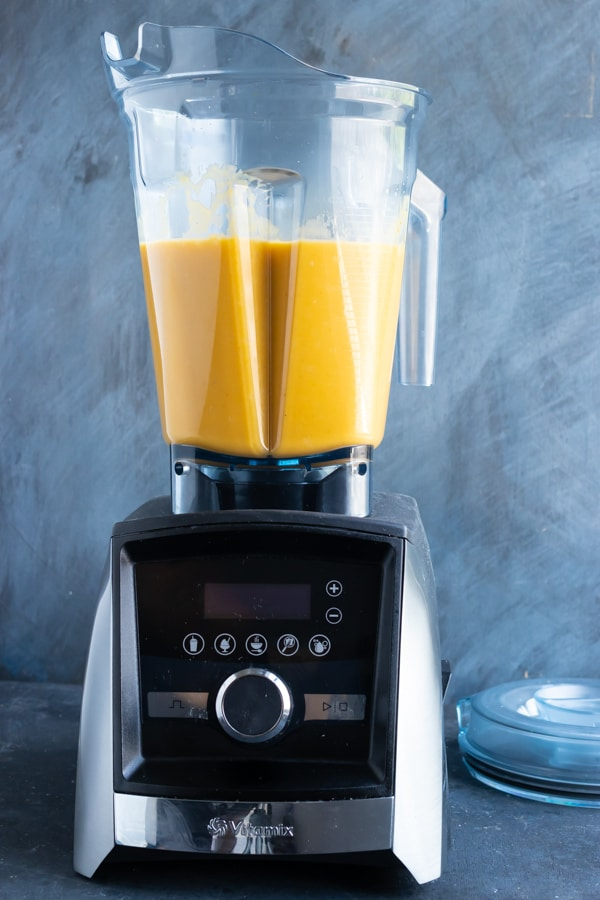 Butternut squash soup being blended until creamy in a Vitamix high-speed blender.