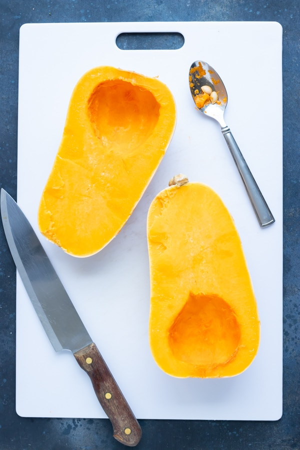 A butternut squash that has been cut in half and the seeds scooped out.