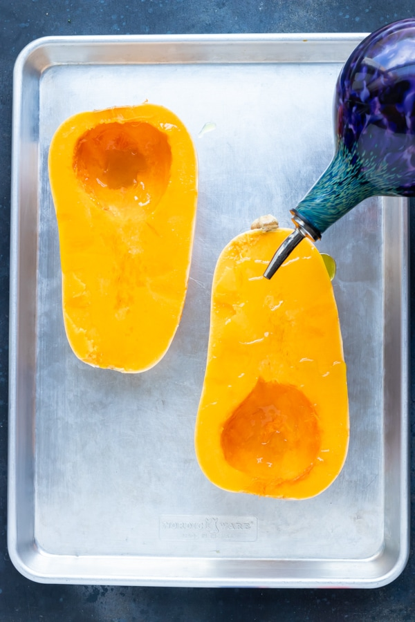 Oil being drizzled on the two halves of a butternut squash.