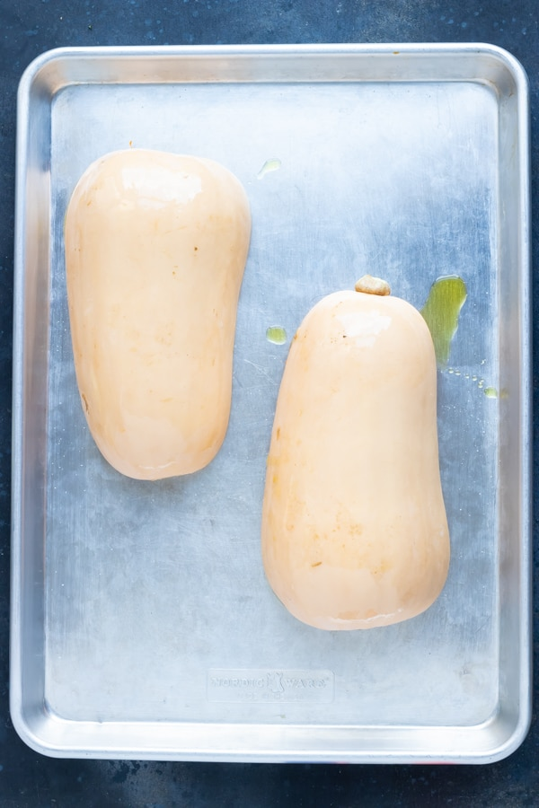 Two halves of a butternut squash face-down on a baking sheet to be roasted.
