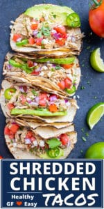 Four shredded chicken tacos in a row with tomatoes an avocado next to lime wedges.