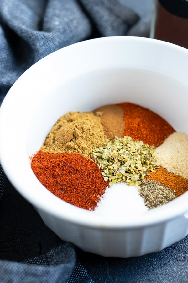 Spices in a white bowl showing how to make homemade chili seasoning.