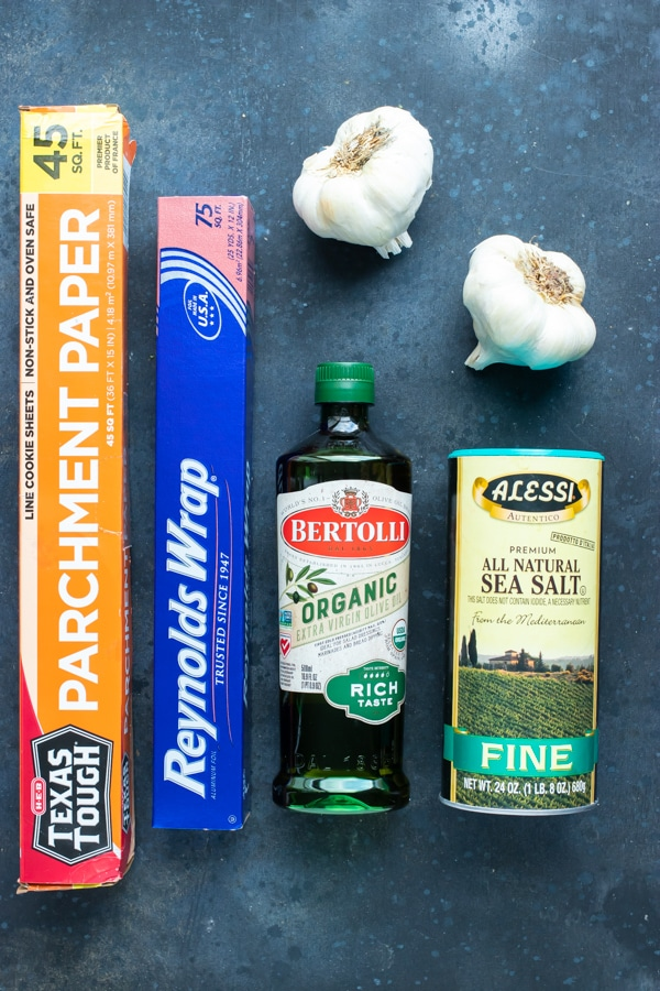 Heads of garlic, oil, salt, parchment paper, and aluminum foil as the ingredients and tools needed for a roasted garlic recipe.