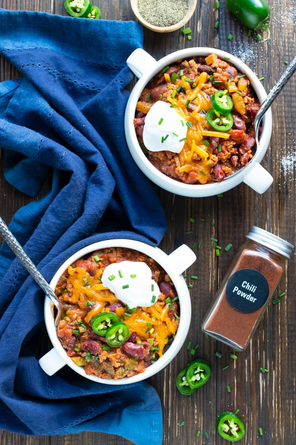 Two bowls that are filled with healthy turkey chili with a blue napkin.