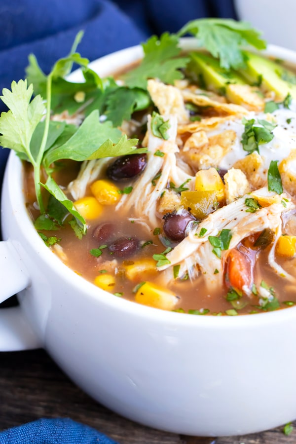 One of the best healthy soup recipes for a crockpot tortilla soup in a white bowl with tortilla chips and cilantro on top.