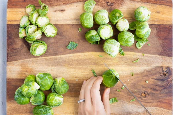 A wooden cutting board with Brussels sprouts that are getting the ends trimmed off with a knife.
