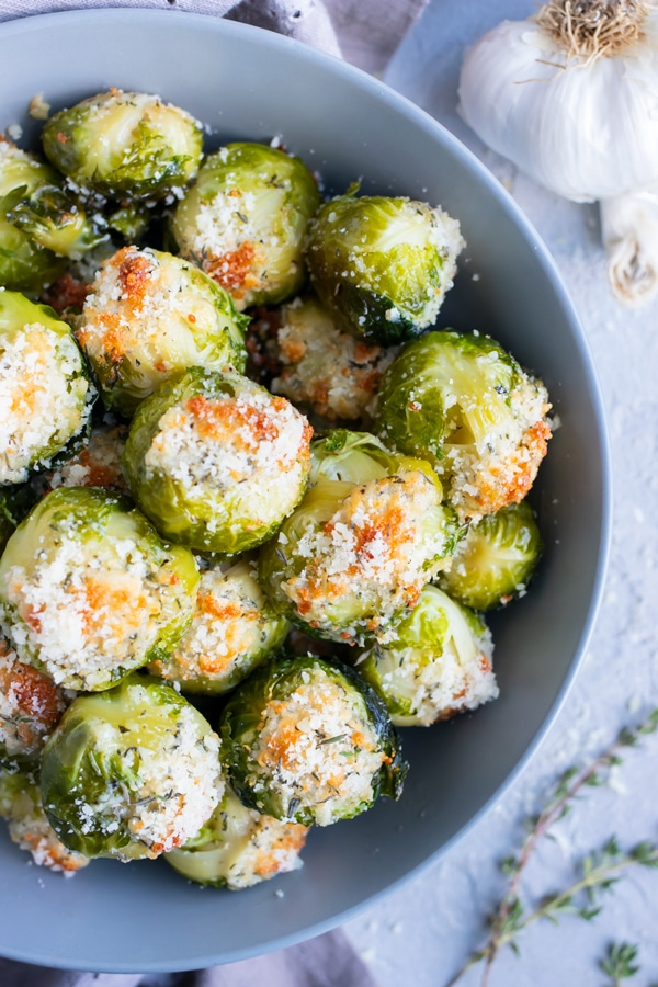 The best vegan crispy smashed Brussels sprouts with Parmesan cheese, garlic, and herbs in a grey bowl.