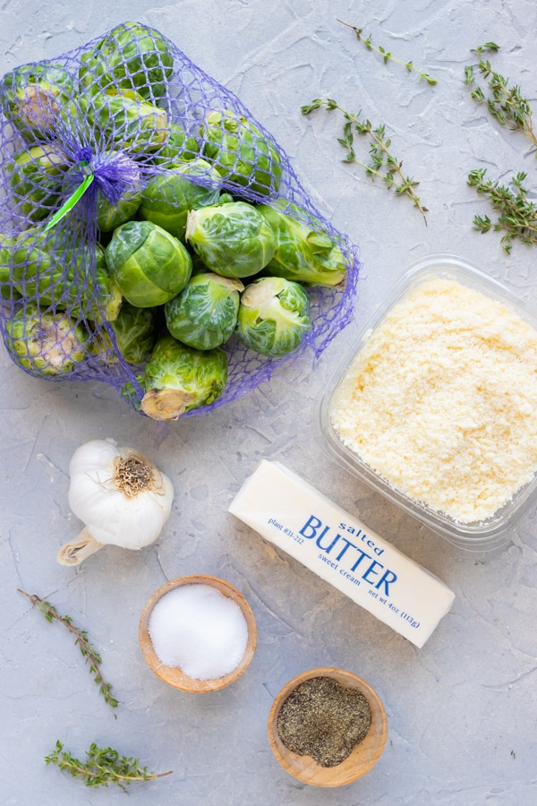 A one pound bag of Brussels sprouts, Parmesan cheese, butter, garlic, and herbs as the ingredients in a roasted Brussels sprouts recipe.