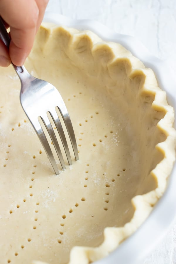A fork piercing holes in the bottom of a gluten-free pie crust.