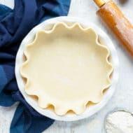 A white 9-inch pie plate full of crust dough.