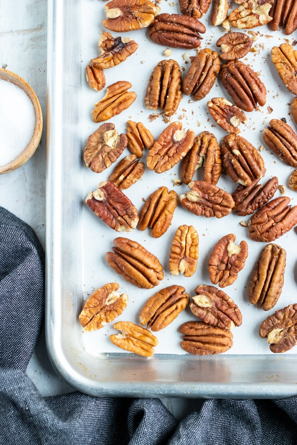 A baking sheet with a layer of pecans showing how to toast pecans in the oven.