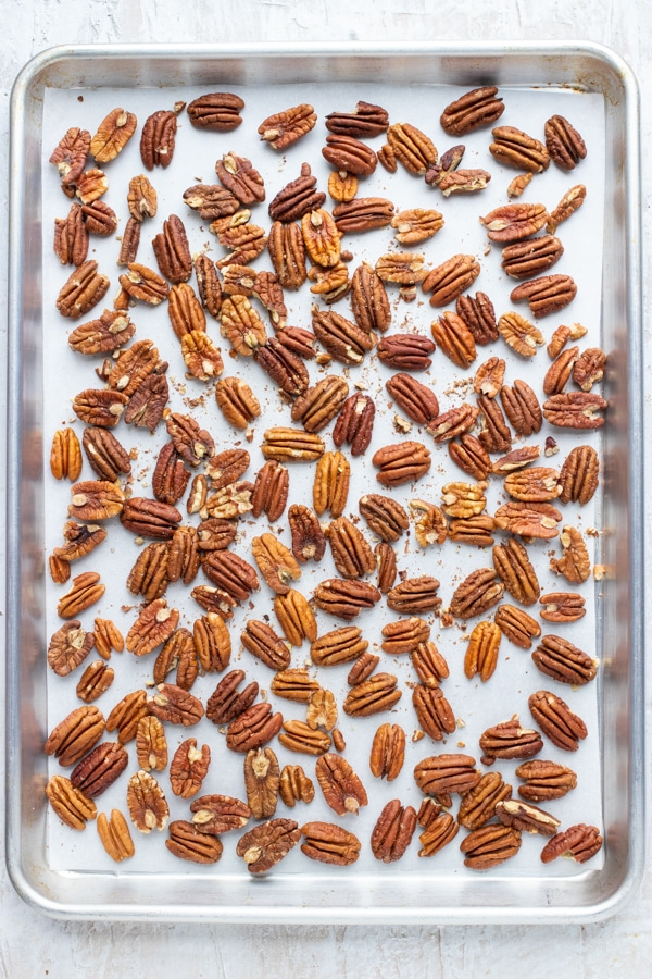 A baking sheet with a layer of pecans showing how to roast pecans in the oven.