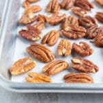 Toasted pecans on a baking sheet with parchment paper.