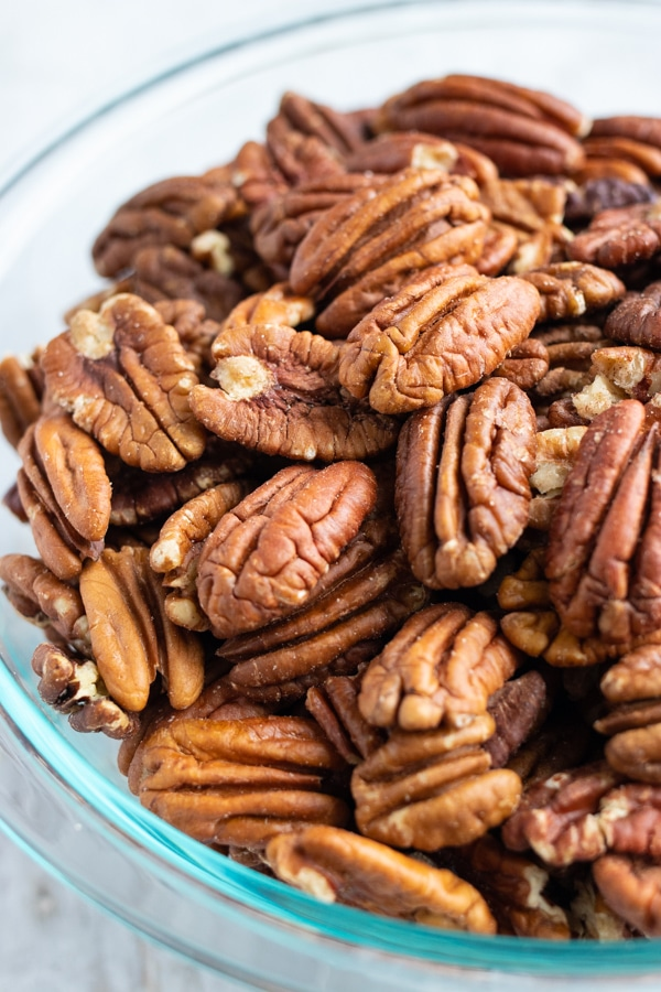 A clear bowl full of raw pecans before they are toasted in the oven.