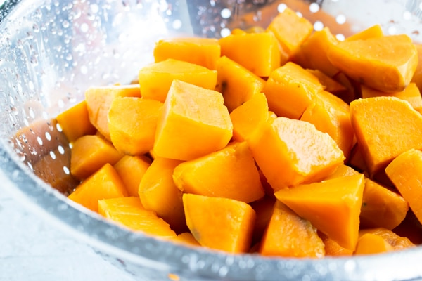 Cooked sweet potatoes in a colander after boiling in water.
