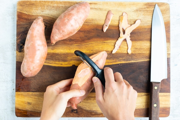 A hand showing how to peel sweet potatoes before boiling in water.