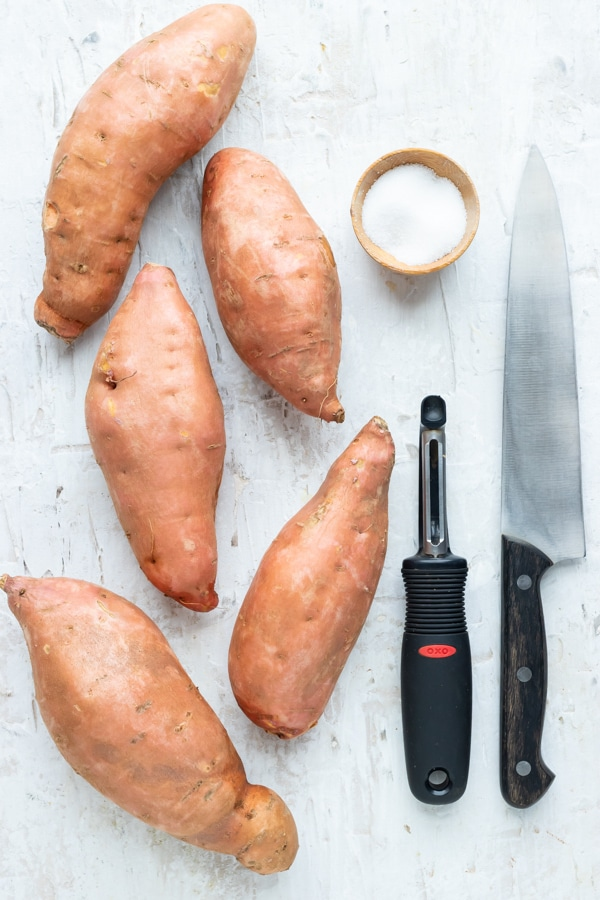 Sweet potatoes, a potato peeler, a knife, and salt as the tools and ingredients for boiling sweet potatoes.