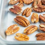 Toasted pecans on a large baking sheet that are going to be roasted in the oven.