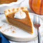 A slice of the best homemade pumpkin pie recipe with whipped cream and cinnamon sticks next to it.