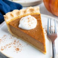 A slice of the best pumpkin pie recipe from scratch with whipped cream and cinnamon sticks next to it.
