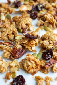 Big clusters of granola on a parchment paper lined baking sheet.