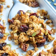 A baking sheet full of an easy and healthy granola recipe with cherries, pecans, and coconut.