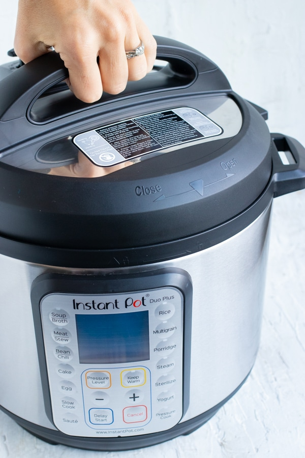 Demonstrating how to remove and put on the lid so it is tightly secured on an Instant Pot.