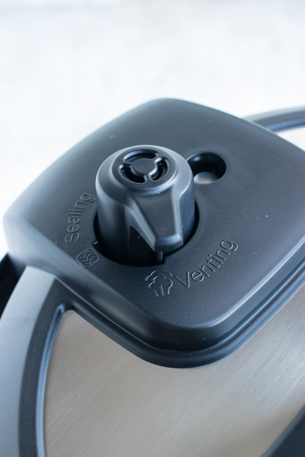 The pressure release valve handle in the venting position of an Instant Pot.