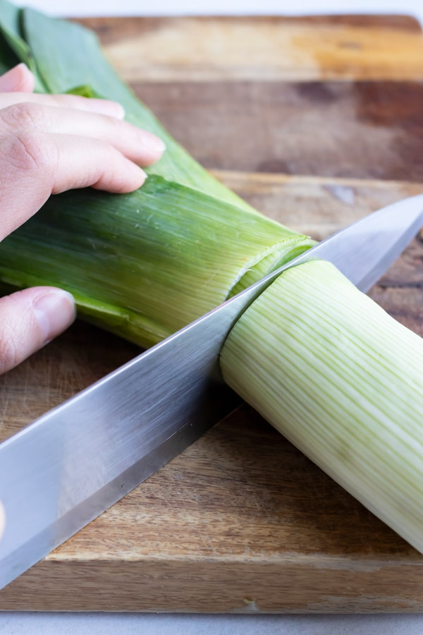 An image showing how to cut fresh leeks to use the white part for soup and discard the green part.