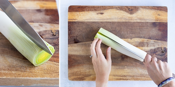 A fresh leek that is being cut down the middle lengthwise.