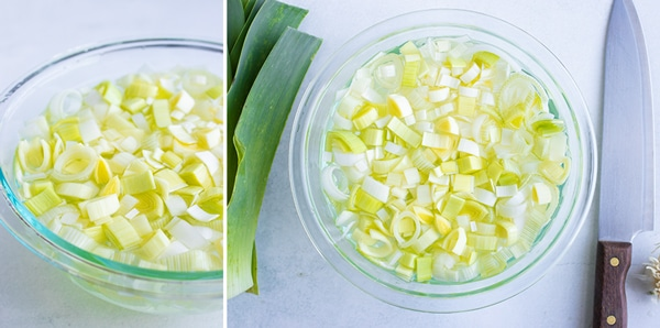 A bowl full of water showing how to clean leeks.