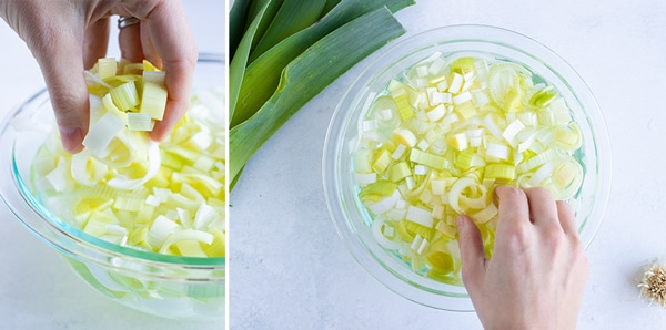 A hand picking up sliced leeks out of a bowl of water after cleaning them.