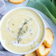 A large soup bowl full of potatoes and leeks blended into a soup being served with toasted baguette bread.
