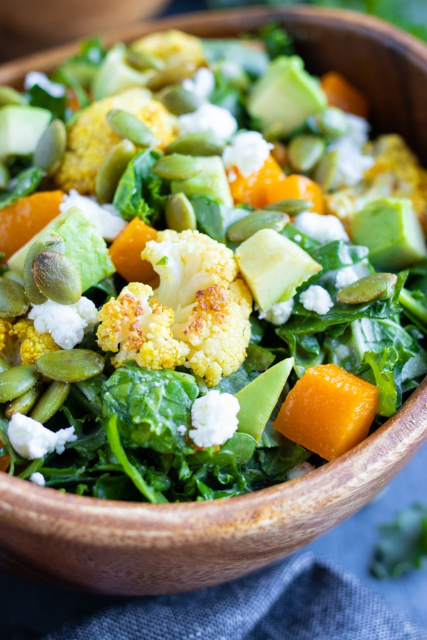 A close up of a floret of roasted cauliflower, avocado, and butternut squash in a chopped kale salad.