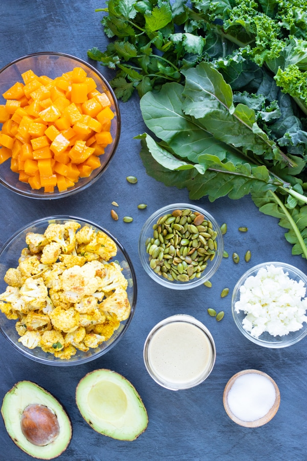 Squash, cauliflower, pumpkin seeds, goat cheese, kale, arugula, and avocado as the ingredients in a roasted vegetable winter salad recipe.