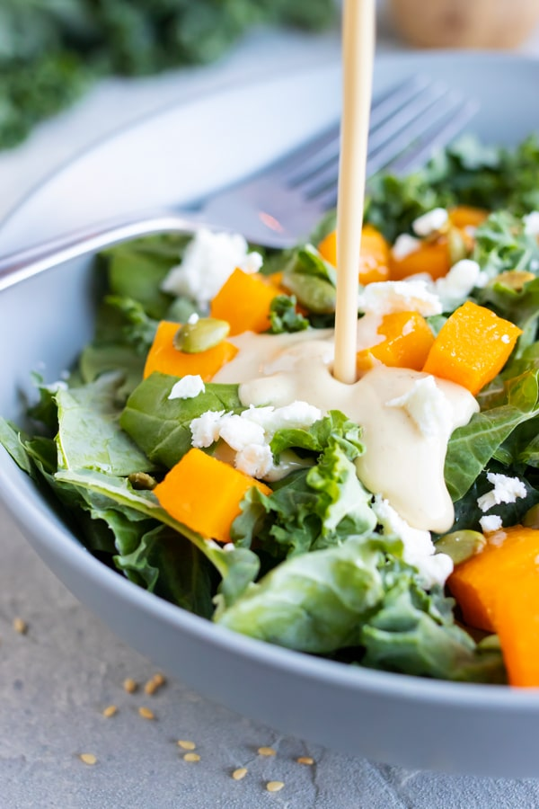 Creamy tahini dressing is poured over a salad