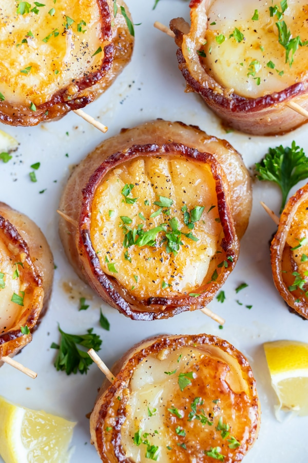 A serving plate full of bacon wrapped scallops for a dinner party appetizer or fancy seafood dinner date.