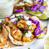 A dinner tray serving roasted cauliflower tacos with a jar full of vegan cilantro cream sauce in the middle with limes.