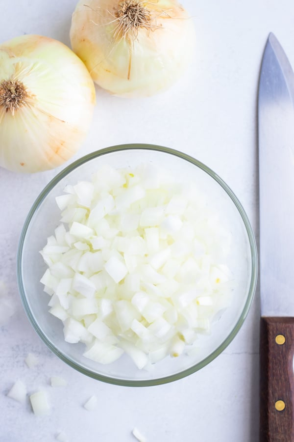 A bowl of diced onion sits on a white cutting board next to a sharp chef knife.