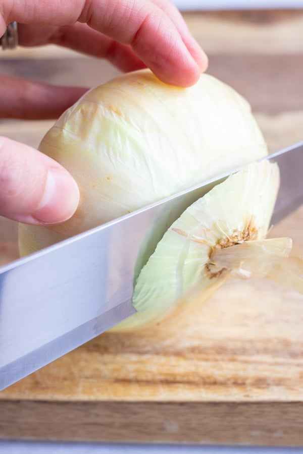 Cutting the ends off of an onion to slice and dice it.