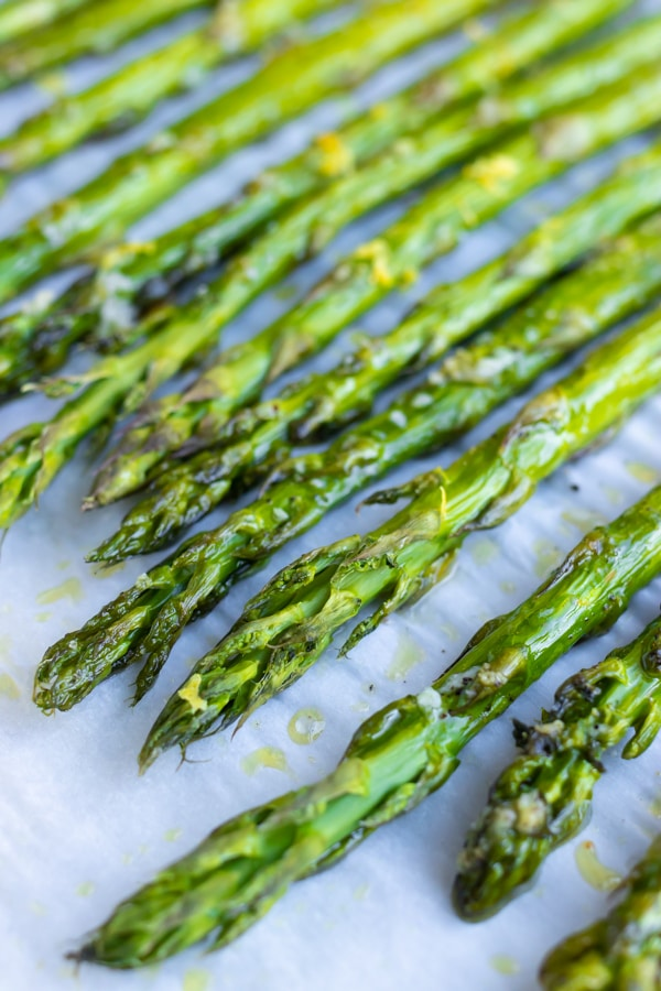 Bright green asparagus that has been baked on a baking sheet in the oven.