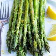 Oven-roasted asparagus with lemon and garlic sauce on a white serving plate.
