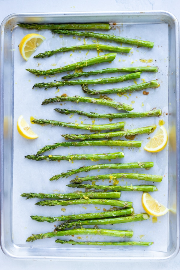 Roasted garlic asparagus with fresh lemon juice and zest on a large baking sheet.